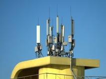 Wiele elektronika anteny na żółtym budynku wierzchołku Fotografia Stock