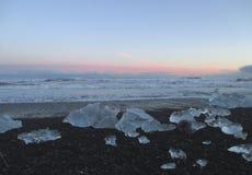 Wiele góry lodowa na czarnym piasku wyrzucać na brzeg pod pięknym zmierzchu niebem Fotografia Stock