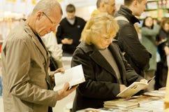 Wiele goście trzyma książki w bookstore Zdjęcie Stock