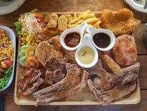 Wiele jakby stek w drewno talerzu tak jak wieprzowina, kość, kurczak zdjęcie stock