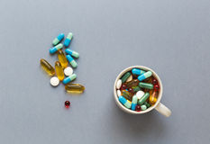 Wiele kolorowe pigułki w filiżance na szarym tle Fotografia Royalty Free