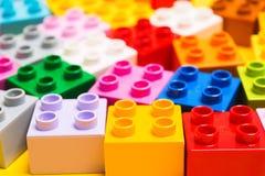 Wiele kolorowe plastikowe cegły zabawkarski dziecko konstruktor na żółtym tle obrazy stock