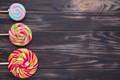 Wiele kolorowi lizaki na brązu drewnianym tle fotografia stock