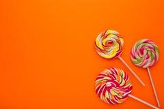 Wiele kolorowi lizaki na pomarańczowym tle, cukierki zdjęcie royalty free