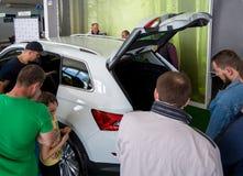 Wiele ludzie considering nowego samochód w sala wystawowej Obraz Stock