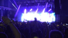 Wiele ludzie macha ręki wpólnie, cieszący się muzykę przy zespołu rockowego koncertem, mo zbiory wideo