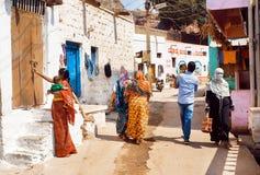 Wiele ludzie na wąskiej ulicie z ceglanymi wiejskimi domami miasteczko w Karnataka stanie Zdjęcia Stock