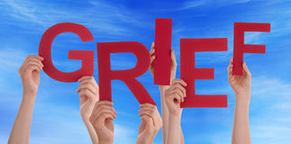Wiele ludzie ręk Trzyma Czerwonego słowo żalu niebieskie niebo zdjęcia stock