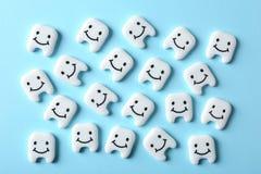 Wiele mali plastikowi zęby z ślicznymi twarzami na koloru tle zdjęcie royalty free