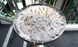 Wiele Papierosowi krupony w piasku na ashtray Obrazy Stock