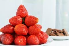 Wiele przy bielu talerzem blisko do filiżanki chokolate na stole w lekkim pokoju czerwona dojrzała jucy truskawka Obrazy Stock