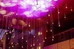 Wiele round lampy pod sufitem Rozjarzone lampy w ciemnym modnym wnętrzu Białe lub lekkie lampy jarzą się na zmrok barwiącym tle Zdjęcia Royalty Free
