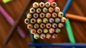 Wiele stubarwni ołówki ruszają się w okręgu na czarnym drewnianym tle z markierami Pojęcia biuro lub szkoła, wiedza dzień zbiory wideo