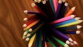 Wiele stubarwni ołówki w czarnym szklanym ruchu w okręgu na czarnym drewnianym tle Pojęcia biuro lub szkoła, wiedza dzień, zdjęcie wideo