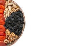 Wiele wysuszone owoc na round drewnianym talerzu, nerkodrzew dokrętki, przycinają, figi, rodzynka i morele odizolowywający na bie obraz royalty free