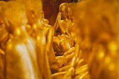 Wiele złota Buddha statua punkt ostrość w jeden pięknej Buddha statui w starej świątyni, pokojowy i święty Obrazy Royalty Free