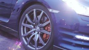 Wielenschijf van donkerblauwe nieuwe auto in zonnestralen presentatie koplampen auto Koude schaduwen stock videobeelden