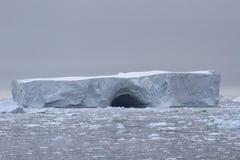 Wielka łomota góra lodowa na chmurzącym dniu przy wybrzeżem anty Zdjęcie Stock