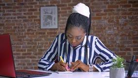 Wielka afrykańska dziewczyna sprawdza jej laptop i pisze dokumentach zaraz po na jej pracującym biurku wśrodku cegły podczas gdy