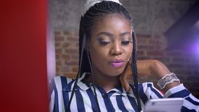 Wielka afrykańska kobieta patrzeje dokładnie przy smartphone podczas gdy siedzący w ceglanym studiu