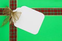 Wielka Bożenarodzeniowa prezent etykietka z czerwonym i złocistym faborkiem na zielonym opakunkowego papieru tle Obraz Stock