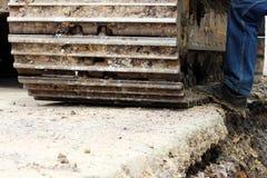 Wielka budowy bagrownica która pracuje na drogowym remontowym miejscu i kierowca stopie która siedzi w kokpicie reportaż shorttin obrazy stock