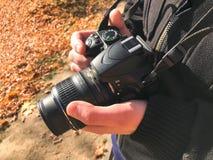 Wielka czarna nowożytna cyfrowa lustrzana fachowa kamera w rękach fotograf Mężczyzny fotograf przystosowywa kamerę obrazy stock
