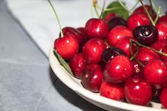 Wielka czerwień i zmrok - czerwone wiśnie w stalowym kubku na szarości i, kamienny tło zdjęcie royalty free