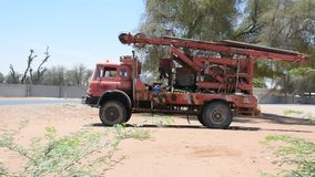 Wielka czerwona stara antykwarska psująca się wodna maszyny ciężarówka parkująca w piasku drzewami w Zjednoczone Emiraty Arabskie zdjęcie wideo