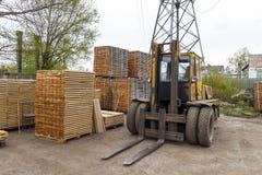 Wielka dźwignięcie ciężarówka i sterty nowe drewniane deski i stadniny przy th Obrazy Royalty Free