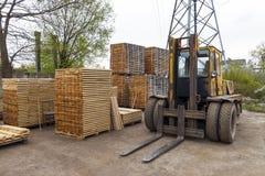 Wielka dźwignięcie ciężarówka i sterty nowe drewniane deski i stadniny przy th Zdjęcia Royalty Free