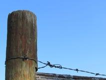 Wielka Drewniana Płotowa poczta, drut kolczasty i niebieskie niebo, Fotografia Stock