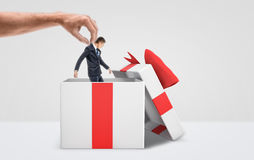 Wielka męska ręka dostaje malutkiego biznesmena out od białego prezenta pudełka z czerwonym łękiem na białym tle Zdjęcie Stock