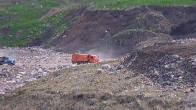Wielka pomarańczowa śmieciarska ciężarówka nalewa grat na śmieciarskim usypie zdjęcie wideo