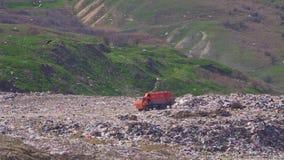 Wielka pomarańczowa śmieciarska ciężarówka nalewa grat na ogromnym śmieciarskim usypie zdjęcie wideo