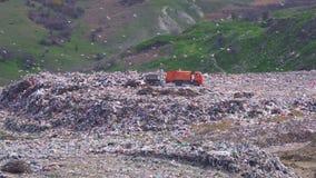 Wielka pomarańczowa śmieciarska ciężarówka nalewa grat na toksycznym śmieciarskim usypie zbiory wideo