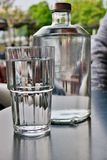 Wielka przejrzysta butelka woda z szklany nast?pnym, w g?r? zdjęcia royalty free