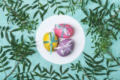 Wielkanoc barwił jajka dekorujących z faborkiem na kwiecistym tle Obrazy Stock