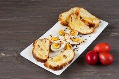 Wielkanoc barwił jajka i pokrajać Wielkanocnego chleb w bielu talerzu na popielatej drewnianej desce Zdjęcie Royalty Free