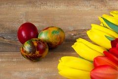 Wielkanoc barwił jajka i tulipany na brown drewnianej desce żółtych i czerwonych Obraz Stock