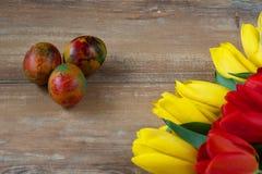 Wielkanoc barwił jajka i tulipany na brown drewnianej desce żółtych i czerwonych Zdjęcie Stock