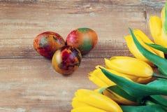 Wielkanoc barwił jajka i tulipany na brown drewnianej desce żółtych i czerwonych Fotografia Royalty Free