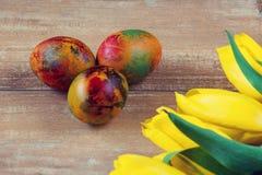 Wielkanoc barwił jajka i tulipany na brown drewnianej desce żółtych i czerwonych Zdjęcie Royalty Free