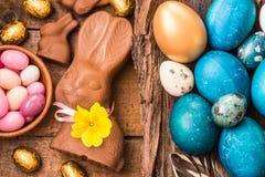 Wielkanoc barwił jajka, czekoladowego królika i cukierki na nieociosanym drewnianym tle, Obrazy Royalty Free