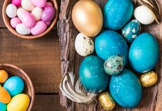 Wielkanoc barwił jajka i cukierki na nieociosanym drewnianym tle Zdjęcie Royalty Free