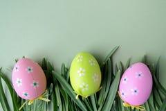 Wielkanoc barwił jajka w trawie na zielonym tle Odgórny widok Obrazy Stock