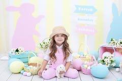 Wielkanoc! Dziewczyna bawić się z Wielkanocnym królikiem Dziecko trzyma królika w jego rękach przeciw tłu Wielkanocny wnętrze fotografia royalty free