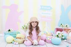 Wielkanoc! Dziewczyna bawić się z Wielkanocnym królikiem Dziecko trzyma królika w jego rękach przeciw tłu Wielkanocny wnętrze zdjęcia royalty free