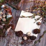 Wielkanoc list dekorujący z przepiórek jajkami, gnezom, mech, piórka, sosna konusuje i kapuje wierzba na drewnianym tle Zdjęcia Stock
