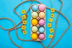 Wielkanoc protestuje kolorowych jajka w pudełku na błękitnym tle otaczającym arkaną obrazy stock